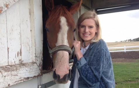 Senior Emma O'Brien poses with her horse Sucré Pois (Sweet Pea) outside of Copenhagen, Denmark.