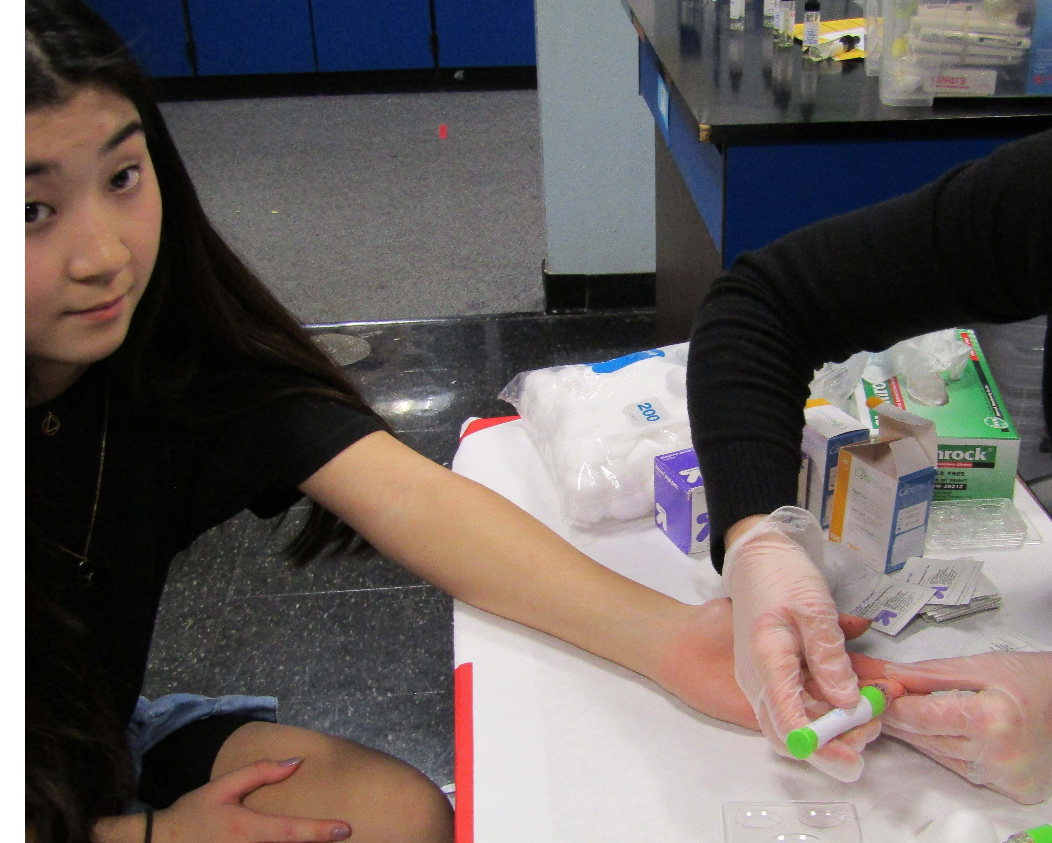 Junior Anna Seiki gets her finger pricked at annual physiology class blood testing.