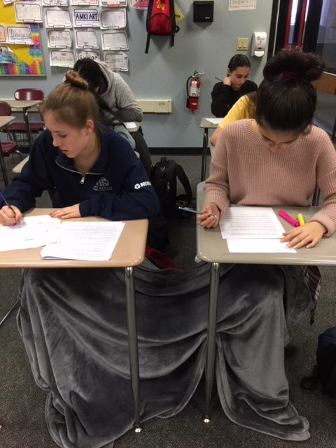 Nelmarie De Jager and Elise Garcia stay warm on Dec. 22 during their freshman English final, with Eliana Goldstein in the back right. For the first time, finals took place the three days before winter break. School is scheduled to start Aug. 16 in order for fall semester to finish in December 2018.
