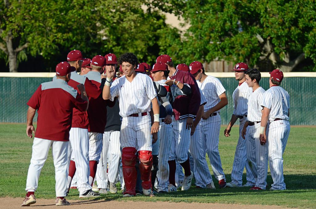 Varsity baseball celebrates on the field after a 5-3 win over College Park May 10. The game was also Senior Night., a recognition of the team's nine seniors on their last home game.
