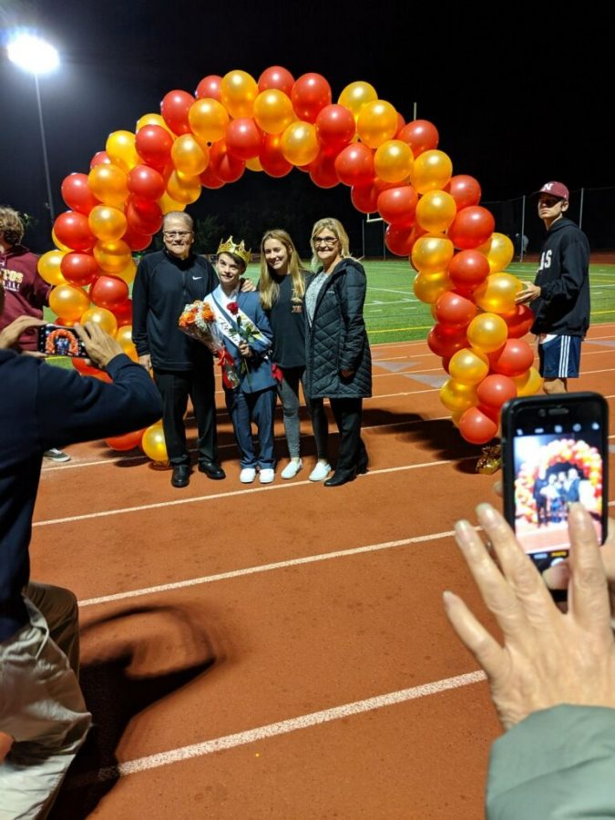 Gus Xepoleas, voted Homecoming King by his classmates, is escorted by his sophomore sister, Grace, and his parents, Thomas and Holly, at the Homecoming football game Friday Sept. 29, 2019.