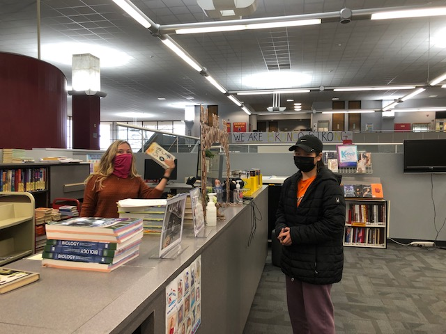 Principal Kelly Cooper helps freshman Angelina Chen check out a novel for her English class on Jan. 12. Students are in distant learning until at least March, but occasionally come to campus for materials and books.